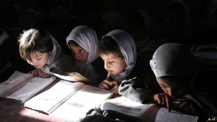 Afghan school girls are hunched over books