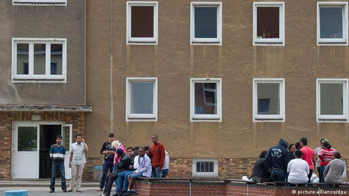 Asylum seekers in front of a home (Photo: Patrick Pleul)
