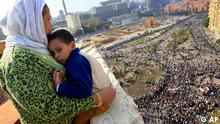 An Egyptian mother hugs her child as she looks down from a balcony at thousands of Egyptian protesters gathered at Tahrir Square in Cairo, Egypt in January 2011 Copyright: Amr Nabil, File/AP/dapd