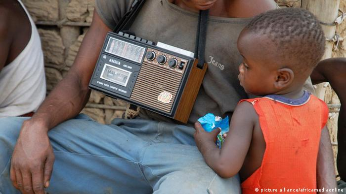 An African child listening to an old radio