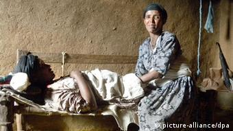 A pregnant Ethiopian woman lying on her bed in a simple room with her midwife. (Photo: Eva Krafczyk)