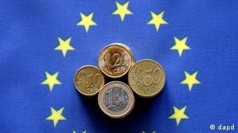 Euro coins on top of an EU flag