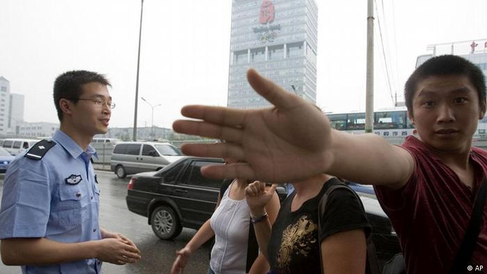 A plainclothes officer tries to prevent a photographer from taking a photo (Photo: ddp images/AP Photo/Ng Han Guan)