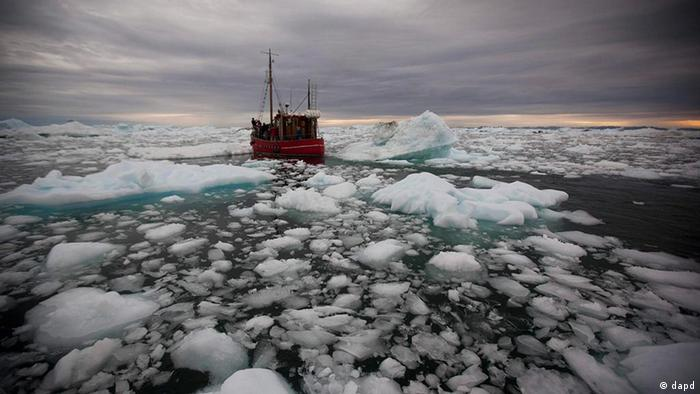 A boat steers slowly through floating ice, left over from broken-up icebergs shed from the Greenland ice sheet