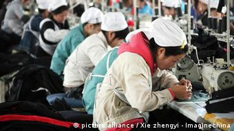 Female Chinese workers make clothing to be exported .
