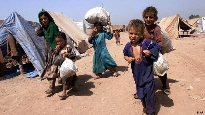 Newly-arrived Afghan refugee children carry their belongings through the Jalozai refugee camp, Pakistan, in this Monday, Sept. 17, 2001. (Photo: AP)