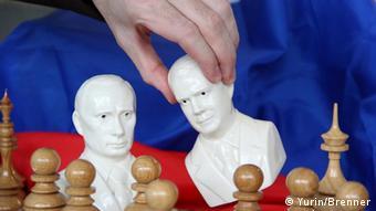 Рука поднимает фарфоровый бюст Медведева с шахматной доски. На ней стоят шахматные фигуры. Сзади - российский флаг.