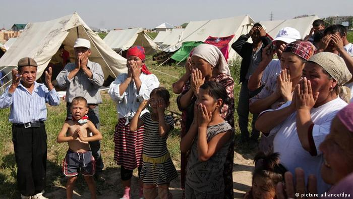Kyrgyz people pray in a Kyrgyz refugee camp outside the city of Osh in the southern Kyrgyzstan 23 June 2010.