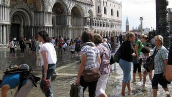 Tourists caught by high tide in front of St Mark's Basilica ('Jean Di Marino') 3. Conservationists say the volume of tourist traffic, the increased development it entails, and rising water levels, are endangering Venice like never before.