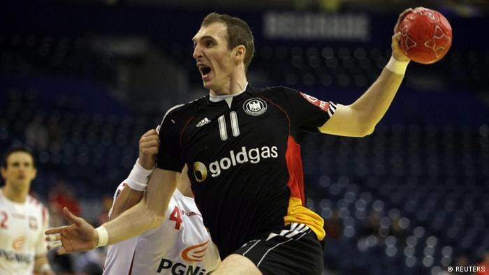 Germany's Holger Glandorf, center, runs with the ball past Poland's Patryk Kuchczynski, back, during their Men's European Handball Championship Group 1 match in Belgrade, Serbia, Wednesday, Jan. 25, 2012. Photo:Marko Drobnjakovic/AP/dapd