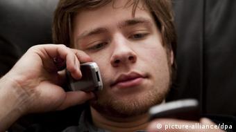Ein Jugendlicher telefoniert mit einem Handy und surft gleichzeitig mit dem anderen Handy (Foto: dpa)