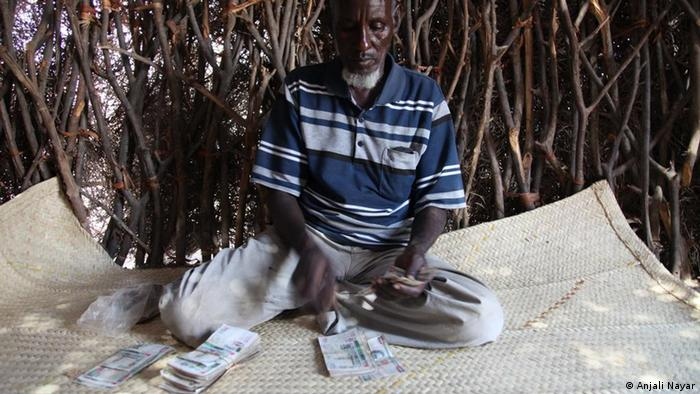 Abdoulai Mohamed counting cash in his hut in Loruth, Turkana