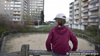 Ein kleiner Junge sitzt allein auf dem Holzgeländer eines Spielplatzes im Innenhof eines Plattenbau-Wohngebiets in Frankfurt (Oder), aufgenommen am 08.04.2008 (gestelltes Symbolbild zum Thema Kinderarmut). Foto: Patrick Pleul +++(c) dpa - Report+++