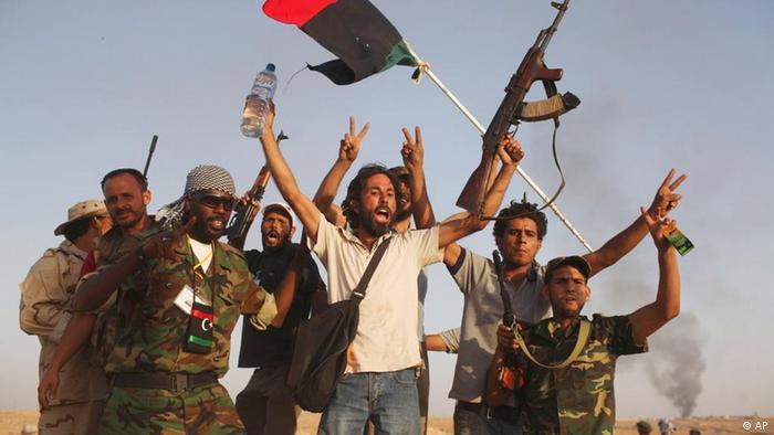 گروهی از شورشیان مسلح لیبی پس از پیروزی بر نیروهای قذافی در بنی ولید