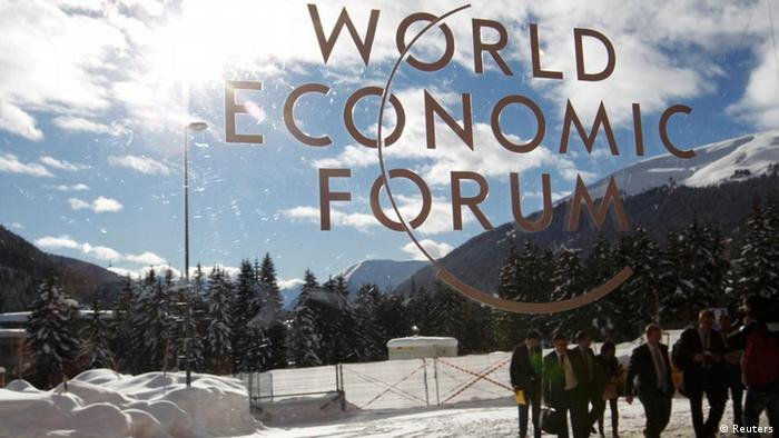 Visitors are reflected in window of the congress center, venue of the World Economic Forum (WEF) in Davos, January 26, 2012. REUTERS/Arnd Wiegmann (SWITZERLAND - Tags: POLITICS BUSINESS)