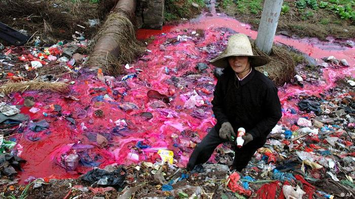 China: a woman collects plastic bottles near a river where water is polluted with a reddish dye directly discharged from a small paper factory nearby