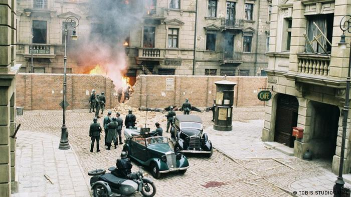 film scene from 'The Pianist' shows a building on fire while army officers look on (TOBIS STUDIOCANAL)
