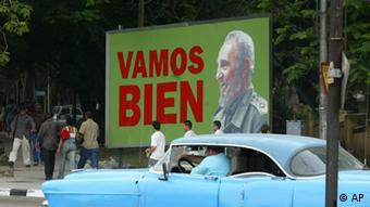 An old American car passes next to a giant poster with Fidel Castro's image that reads Vamos Bien (We Go Well), on the streets of Havana, Cuba, Monday, March 28, 2005. Cuban President Fidel Castro announced last week the reappraisal of the Cuban currency of 7% and he promised an improvement in the quality of life for Cubans. (AP Photo/Jorge Rey) **EFE OUT**