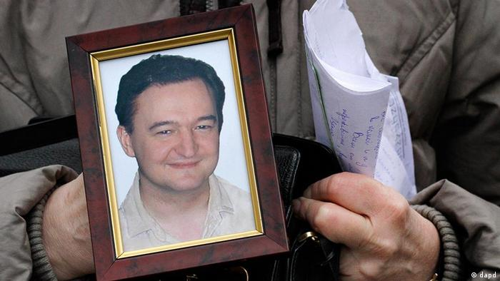 Hands holding photo portrait of lawyer Sergei Magnitsky