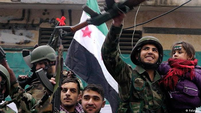 Syrian soldiers, who have defected to join the Free Syrian Army, hold up their rifles and wave Syrian independence flags, during a protest against Syria's President Bashar al-Assad in Khalidieh, near Homs January 26, 2012. Picture taken January 26, 2012. REUTERS/ Stringer (SYRIA - Tags: POLITICS CIVIL UNREST MILITARY)