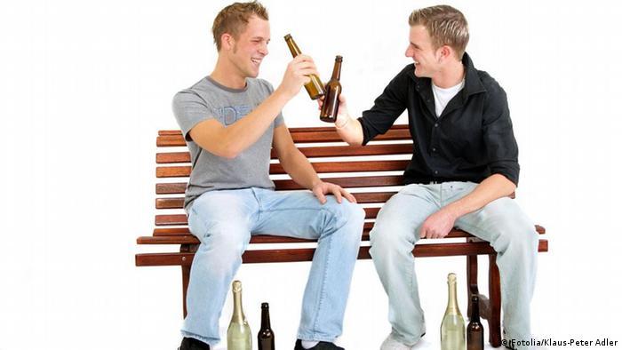 Dois homens sentados sobre um banco bebendo cerveja