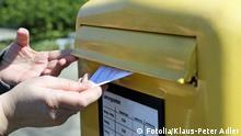 Zwei Hände öffnen einen Briefschlitz und werfen einen Brief ein