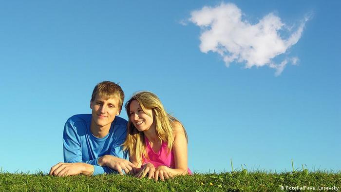 Symbolbild Liebe Glück Paar auf Wiese und blauer Himmel