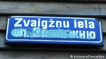 Blue street sign with white writing in Latvian
