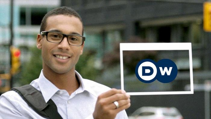 A person holding a sign with Deutsche Welle's new logo