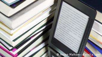 An e-book reader next to a stack of printed books