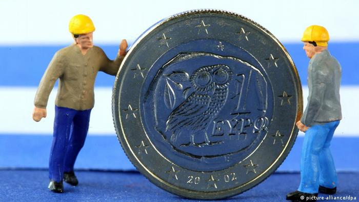 Two miniature figures roll a euro coin against the backdrop of the Greek flag