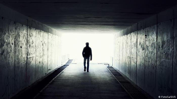 Homem caminha em direção a luz no fim de túnel