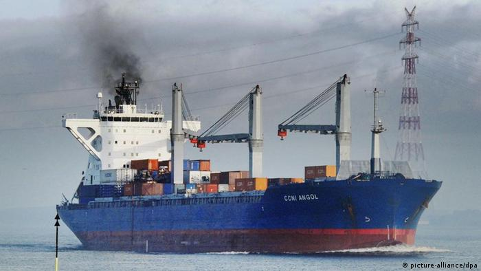 A container ship with a dark cloud rising from its smoke stack