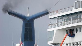 Smoke rises from a smoke stack on a ship