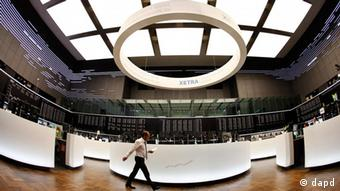 A trader walks through a stock trading hall in Frankfurt