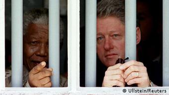 Nelson Mandela with Bill Clinton behind the bars of his Robben Island cell in 1998