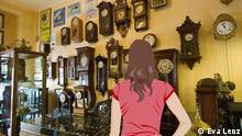 Anna steht in einem Geschäft und betrachtet altmodische Uhren an der Wand.
