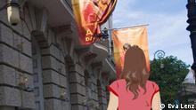Anna geht an einem Gebäude mit orangen Fahnen entlang.