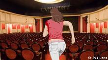 Anna rennt durch einen Theatersaal mit roten Sitzen.