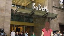 Anna steht vor dem Eingang des Kaufhauses KaDeWe.
