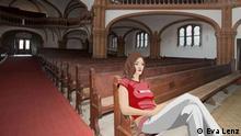 Anna sitzt auf einer Kirchenbank.