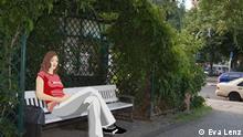 Anna sitzt an einer Straße auf einer Bank unter einem Dach aus Efeu.