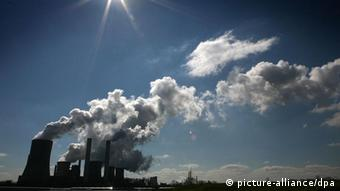 Smoke billowing from tail pipes of energy factories