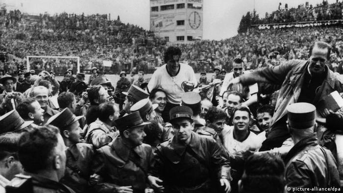 Kapitän Fritz Walter (M.) und Trainer Sepp Herberger (r.) werden am 4.7.1954 in Bern nach dem Sieg über Ungarn im Endspiel der Fußball- Weltmeisterschaft 1954 auf den Schultern von begeisterten Anhängern getragen. Walter, Ehrenspielführer der Nationalmannschaft, ist am 17.6.2002 im Alter von 81 Jahren gestorben. Dies teilte der Pressesprecher des 1. FC Kaiserslautern, Nowak, mit. Er sei um 15.15 Uhr in seinem Haus in Alsenborn friedlich eingeschlafen. Walter führte 1954 die Nationalmannschaft zum 3:2 über Ungarn und damit zum ersten von drei Weltmeisterschafts-Titeln des Deutschen Fußball- Bundes (DFB). Der Pfälzer war während seiner Karriere im Nationalteam, für die er 61 Länderspiele bestritt und in der er 33 Tore schoss, die rechte Hand von Erfolgstrainer Herberger auf dem Spielfeld.
