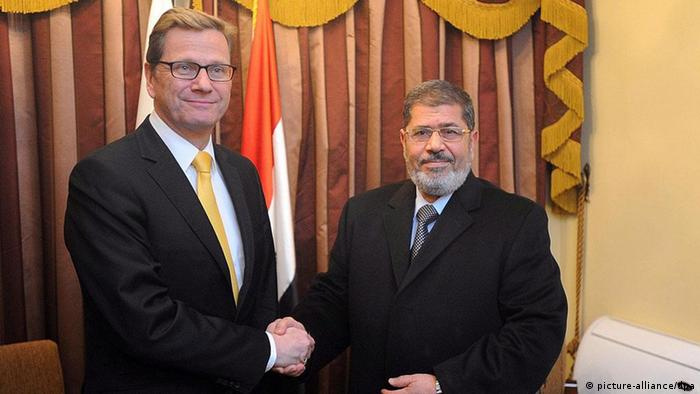 epa03086285 German Foreign Minister Guido Westerwelle (L) shakes hands with the leader of the Muslim Brotherhood's Freedom and Justice Party (FJP) Mohammed Morsi (R) in Cairo, Egypt, 30 January 2012. The FJP won the majority of the Egyptian parliament seats in the latest elections, the first ones since the ousting of former President Hosni Mubaral. Westerwelle is on a four-nation regional tour. EPA/mohamed omar