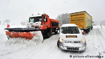 Laster und PKW sowie ein Räumfahrzeug auf einer verschneiten Straße