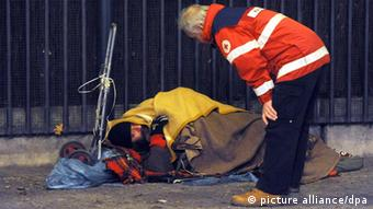 An emergency official speaks with a homeless person in Berlin