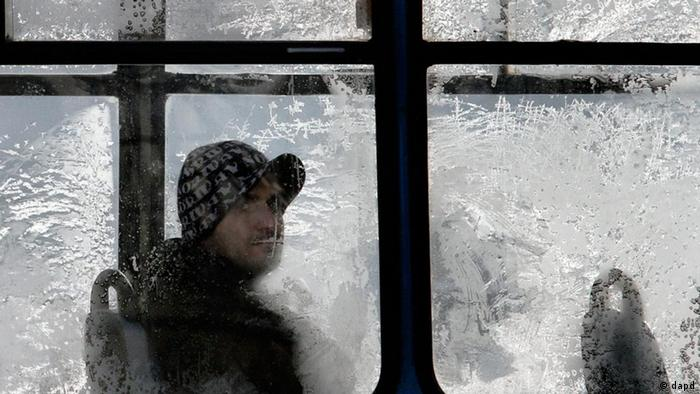A man looks from behind a frosty window on a tram on a cold winters day in Sofia