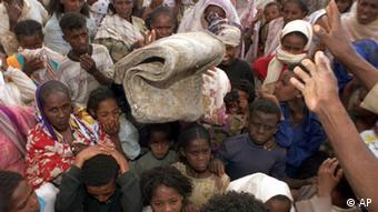 Displaced Eritreans receive blankets at the Dibarwa secondary school, 35 kilometers (22 miles) south of Asmara, Thursday, June 8, 2000. The school shelters some 54,000 people displaced by fighting between Eritrea and Ethiopia. Eritrea acknowledged for the first time that it was asking resident Ethiopians to move into camps for their own protection. (AP Photo/Jean-Marc Bouju)