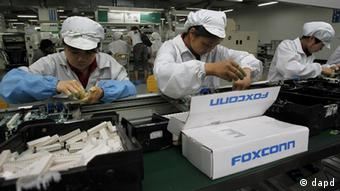 Staff members work on the production line at the Foxconn complex in the southern Chinese city of Shenzhen, Southern city in China, Wednesday, May 26, 2010. The head of the giant electronics company whose main facility in China has been battered by a string of worker suicides opened the plant's gates to scores of reporters Wednesday, hours after saying that intense media attention could make the situation worse. (AP Photo/Kin Cheung)